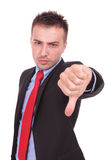 Σοβαρό επιχειρησιακό άτομο που παρουσιάζει τον αντίχειρα κάτω από τη χειρονομία Στοκ Φωτογραφία