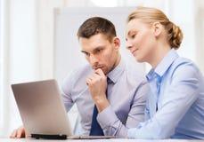 Σοβαρό επιχειρησιακό ζεύγος με το φορητό προσωπικό υπολογιστή Στοκ Φωτογραφία
