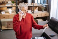 Σοβαρό ηλικιωμένο άτομο που κρατά το τηλέφωνο κυττάρων του Στοκ εικόνες με δικαίωμα ελεύθερης χρήσης