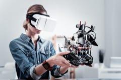 Σοβαρό θηλυκό πρόσωπο που εξετάζει λίγο ρομπότ Στοκ εικόνες με δικαίωμα ελεύθερης χρήσης