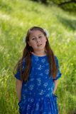 Σοβαρό και στοχαστικό μικρό κορίτσι στο μπλε φόρεμα μπροστά από το χρυσό τομέα στο πάρκο στοκ φωτογραφία