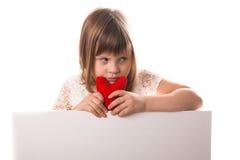 Σοβαρό κοριτσάκι με την κόκκινη καρδιά διαθέσιμη, μια επιγραφή θέσεων Στοκ φωτογραφία με δικαίωμα ελεύθερης χρήσης