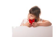 Σοβαρό κοριτσάκι με την κόκκινη καρδιά διαθέσιμη, μια επιγραφή θέσεων Στοκ Εικόνες