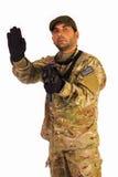 Σοβαρό μέλος των ενόπλων δυνάμεων στρατού που καθιστά το σημάδι στάσεων απομονωμένο στο άσπρο backg Στοκ Φωτογραφία