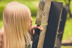 Σοβαρό μικρό κορίτσι που κρυφοκοιτάζει από τον ξύλινο πάγκο Στοκ φωτογραφία με δικαίωμα ελεύθερης χρήσης