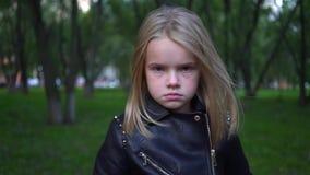 Σοβαρό μικρό κορίτσι σε ένα σακάκι δέρματος που λέει το αριθ. φιλμ μικρού μήκους