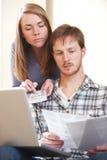 Σοβαρό νέο ζεύγος που φαίνεται στο σπίτι πόροι χρηματοδότησης Στοκ Εικόνα
