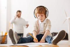 Σοβαρό παιδί που ακούει τη μουσική καθμένος στον πίνακα Στοκ Φωτογραφία