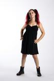 Σοβαρό πανκ κορίτσι στις μπότες αγώνα και το μαύρο φόρεμα Στοκ Εικόνες