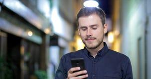 Σοβαρό περπάτημα ατόμων που κοιτάζει βιαστικά στο τηλέφωνο στη νύχτα απόθεμα βίντεο