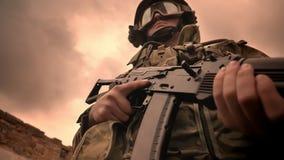 Σοβαρό πρόσωπο του καυκάσιου στρατιωτικού στην κάλυψη, που κρατά gaunand στεμένος κοντά στους τουβλότοιχους έξω, που σκουραίνουν  φιλμ μικρού μήκους