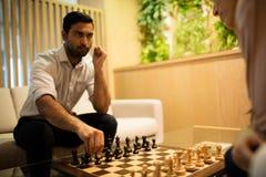 Σοβαρό σκάκι παιχνιδιού επιχειρηματιών με τη γυναίκα συνάδελφος Στοκ Εικόνες