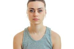Σοβαρό όμορφο κορίτσι πορτρέτου στην γκρίζα μπλούζα που εξετάζει τη κάμερα που απομονώνεται σε ένα άσπρο υπόβαθρο στοκ εικόνες με δικαίωμα ελεύθερης χρήσης