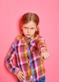 Σοβαρό όμορφο μικρό κορίτσι που δείχνει ένα δάχτυλο σε σας στο ρόδινο υπόβαθρο Στοκ Εικόνα
