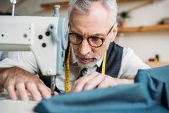 σοβαρό όμορφο ράβοντας ύφασμα ραφτών με τη ράβοντας μηχανή Στοκ Εικόνες