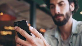 Σοβαρό blogger που χρησιμοποιεί το έξυπνο τηλέφωνο στον καφέ απόθεμα βίντεο