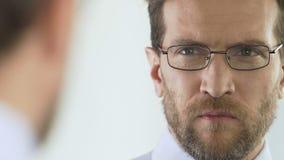 Σοβαρό businessperson που επιλέγει και που φορά eyeglasses στο κατάστημα οπτικής, όραση φιλμ μικρού μήκους