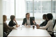 Σοβαρό CEO που οδηγεί την εταιρική συνεδρίαση των ομάδων που μιλά στο multiracia Στοκ φωτογραφία με δικαίωμα ελεύθερης χρήσης