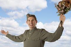 Σοβιετικός στρατιώτης με μια δέσμη των λουλουδιών Στοκ Εικόνα