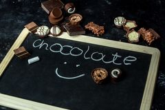Σοκολάτα αγάπης - διαφορετικές, γλυκές πραλίνες του σκοταδιού, του γάλακτος και της άσπρης σοκολάτας σε ένα σκοτεινό, ξύλινο υπόβ στοκ εικόνες με δικαίωμα ελεύθερης χρήσης
