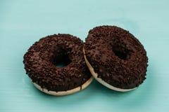 Σοκολάτα δύο donuts σε ένα τυρκουάζ ξύλινο υπόβαθρο Στοκ Εικόνα