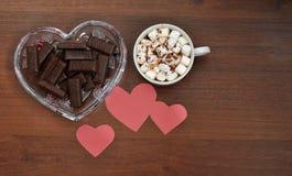 Σοκολάτα, καφές και ρόδινες καρδιές σε ένα ξύλινο υπόβαθρο στοκ εικόνες