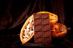 Σοκολάτα με τους λοβούς κακάου στο Μαύρο Στοκ εικόνα με δικαίωμα ελεύθερης χρήσης