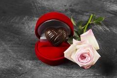 Σοκολάτα υπό μορφή καρδιάς σε μια κόκκινη περίπτωση για ένα δαχτυλίδι, ένα ροζ Στοκ εικόνα με δικαίωμα ελεύθερης χρήσης