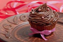 Σοκολάτα cupcake με την κρέμα σοκολάτας, που διακοσμείται με την κορδέλλα, σε ένα καφετί πιάτο με την αγάπη επιγραφής Στοκ Εικόνες