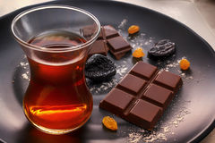 Σοκολάτα, δαμάσκηνα, σταφίδες και τσάι σε ένα γυαλί σε ένα μαύρο πιάτο Στοκ Φωτογραφίες