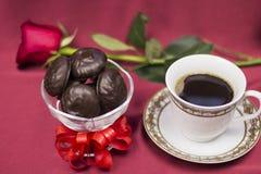 Σοκολάτα και ένα φλιτζάνι του καφέ σε ένα υπόβαθρο των κόκκινων τριαντάφυλλων Στοκ Φωτογραφίες