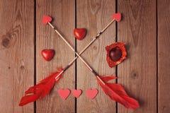 Σοκολάτα και βέλη μορφής καρδιών ημέρας Valentine στο ξύλινο υπόβαθρο Στοκ φωτογραφία με δικαίωμα ελεύθερης χρήσης