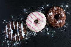 Σοκολάτα και βερνικωμένος donuts, ροζ, λευκό, καφετί στη μαύρη πέτρα, τοπ άποψη Στοκ εικόνες με δικαίωμα ελεύθερης χρήσης