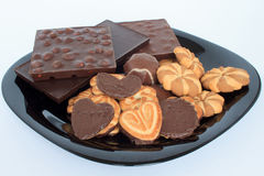 Σοκολάτα και μπισκότα που βρίσκονται στο μαύρο πιάτο Στοκ φωτογραφία με δικαίωμα ελεύθερης χρήσης