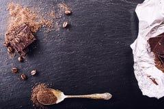 Σοκολάτα μαύρη σοκολάτα Μερικοί κύβοι της μαύρης σοκολάτας με τα φύλλα μεντών Στοκ Εικόνες
