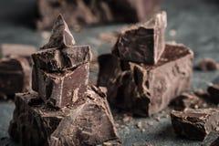 Σοκολάτα μαύρη σοκολάτα Μερικοί κύβοι της μαύρης σοκολάτας Χοντρά κομμάτια σοκολάτας Κομμάτια φραγμών σοκολάτας Στοκ Εικόνες