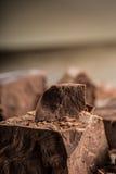 Σοκολάτα μαύρη σοκολάτα Μερικοί κύβοι της μαύρης σοκολάτας Χοντρά κομμάτια σοκολάτας Κομμάτια φραγμών σοκολάτας Στοκ Φωτογραφία