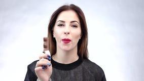 σοκολάτα που τρώει την όμορφη γυναίκα χειλικό κόκκινο Μεγάλα δόντια απόθεμα βίντεο
