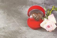 Σοκολάτα υπό μορφή καρδιάς σε μια κόκκινη περίπτωση για ένα δαχτυλίδι, ένα ροζ Στοκ Εικόνες