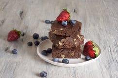 Σοκολάτα - brownie κερασιών που εξυπηρετείται με το βακκίνιο και τη φράουλα στοκ εικόνες
