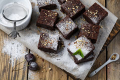 Σοκολάτα brownies με την κονιοποιημένα ζάχαρη και τα κεράσια σε ένα σκοτεινό ξύλινο υπόβαθρο Στοκ φωτογραφίες με δικαίωμα ελεύθερης χρήσης