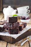 Σοκολάτα brownies με την κονιοποιημένα ζάχαρη και τα κεράσια σε ένα σκοτεινό ξύλινο υπόβαθρο Στοκ εικόνα με δικαίωμα ελεύθερης χρήσης