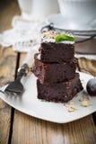 Σοκολάτα brownies με την κονιοποιημένα ζάχαρη και τα κεράσια σε ένα σκοτεινό ξύλινο υπόβαθρο Στοκ Φωτογραφία