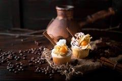 Σοκολάτα cupcakes με την άσπρη βουτύρου κρέμα, που διακοσμείται με το χειμερινό κεράσι σε ένα σκοτεινό ξύλινο υπόβαθρο Διακοσμημέ στοκ φωτογραφία