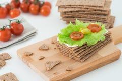 Σουηδικές κροτίδες ψωμιού σίκαλης τριζάτες με το μαλακό τυρί, την άδεια μαρουλιού και τις ντομάτες κερασιών στον ξύλινο πίνακα Στοκ φωτογραφίες με δικαίωμα ελεύθερης χρήσης