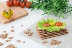 Σουηδικές κροτίδες ψωμιού σίκαλης τριζάτες με το μαλακό τυρί, την άδεια μαρουλιού, τις ντομάτες κερασιών και το δεντρολίβανο στο  Στοκ Εικόνα