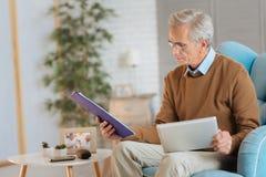 Σοφό συνταξιούχο άτομο που εργάζεται με τα έγγραφα και touchpad Στοκ φωτογραφία με δικαίωμα ελεύθερης χρήσης