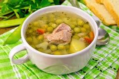 Σούπα από τα πράσινα μπιζέλια με το κρέας στην πράσινη πετσέτα Στοκ εικόνα με δικαίωμα ελεύθερης χρήσης