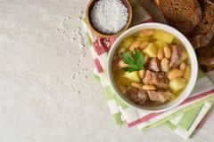 Σούπα βόειου κρέατος με τις πατάτες, τα φασόλια και τα πράσα στο κεραμικό κύπελλο στο υπόβαθρο πετρών Στοκ εικόνες με δικαίωμα ελεύθερης χρήσης