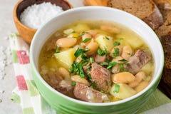 Σούπα βόειου κρέατος με τις πατάτες, τα φασόλια και τα πράσα στο κεραμικό κύπελλο στο υπόβαθρο πετρών Στοκ Φωτογραφία